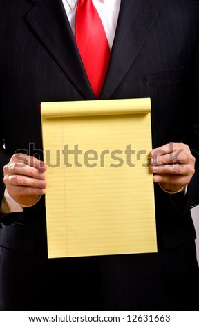 A business man in a blue suit and a red necktie holding a yellow tablet add your own copy or text, business communications