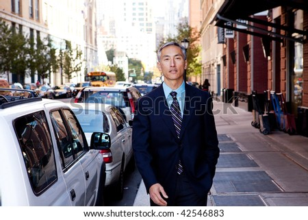 A business man in a city setting on a sidewalk