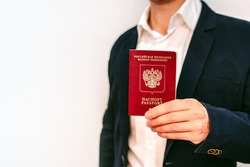 A business man in a jacket and shirt holds a Russian passport