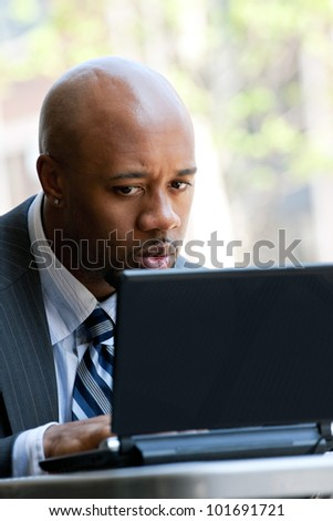 A business man in his early 30s working on his laptop or netbook computer outdoors with a surprised or shocked expression on his face. - stock photo