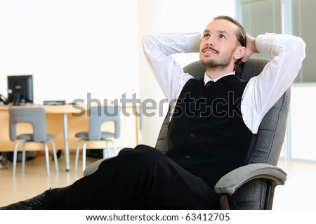 A business man in his office rests in the chair.