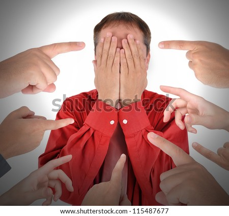 A business man is covering his eyes with his hands and has blame and shame with fingers pointing at him.