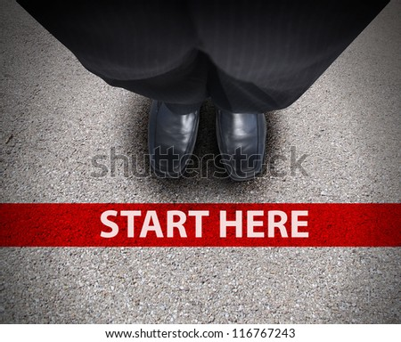 A business man is looking down at his feet with a red race line that says start here to represent a journey,