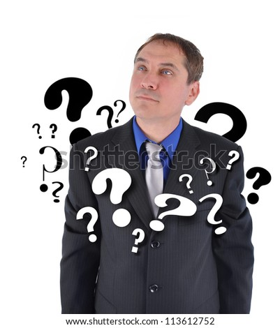 A business man is looking up with question marks around his suit. There is a white background.