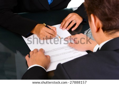 A business man is pointing a place where she should sign the agreement.