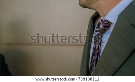 A business man is wearing a grey suite and a purple tie with a grey background in a business park in Majorca, Spain.  #738138112