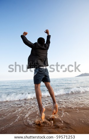 A business man jumping on the beach, freedom, success concept