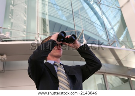 A business man looking into binoculars at his company