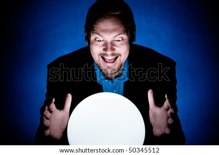 A Business man looking into the future in a crystal ball - stock photo