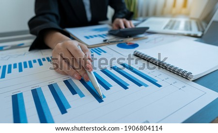 A business man pointing to a graph on the table with a pen and analyzing the graph on the table Stockfoto ©