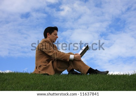 A business man reading a book sitting on the grass