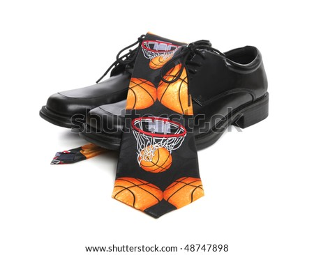 A business man's shoes and a basketball themed tie over white background