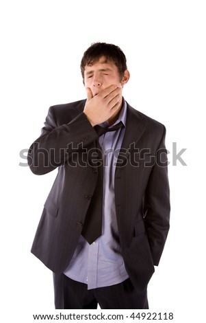 A business man showing how tired he is by rubbing his face.