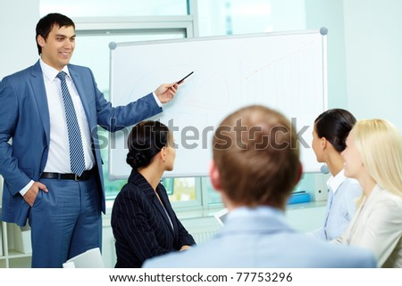 A business man showing something on a whiteboard to his colleagues