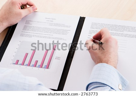 A business man signing a contract on a wooden table