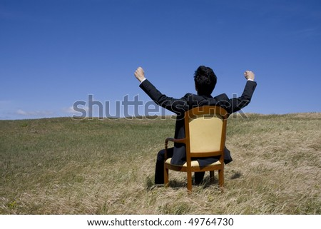 A business man sit on an armchair on the middle of a green field