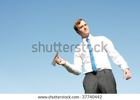 A business man throwing a paper plane