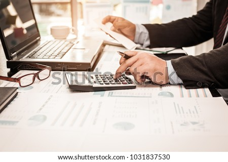 A business man using calculator for calculate expenses bills in his workplace. Business concept.