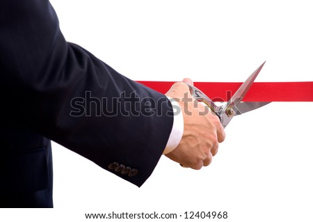 A business man wearing a blue suit cutting a red ribbon with a pair of shiny silver scissors.  Grand opening ceremony or event