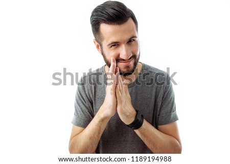 A business man with a beard, a gray t-shirt, with a crafty expression that he came up with, rubbing his hands in front of him, isolated on a white background