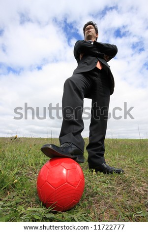 A business man with a red ball on a field