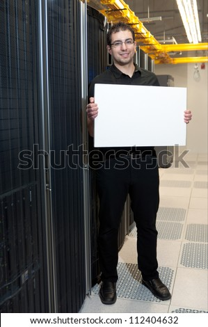 A business man with a satisfied look holding a white board in a datacenter. - stock photo