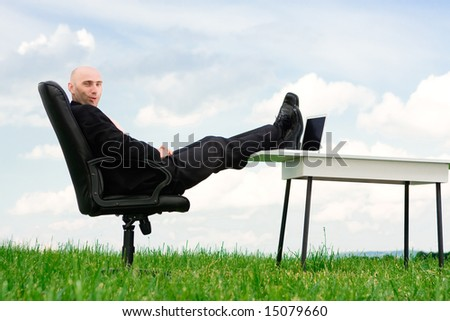 A business man with his feet up on a desk outside.