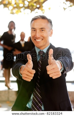 A business man with thumbs up - critical focus on the thumbs