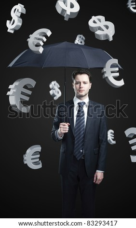 a business man with umbrella under evro and dollar signs rain