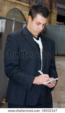 a business man writing on a pad of paper.