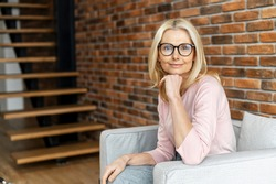 A business portrait of charming middle-aged woman wearing glasses looks at camera, a confident lady sits at armchair at office space, psychologist, consultant. A beautiful friendly blonde indoor