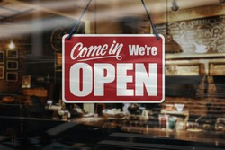 A business sign that says 'Come in We're Open' on cafe/restaurant window