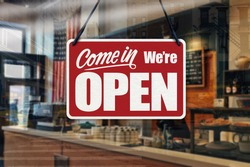 A business sign that says 'Come in We're Open' on cafe/restaurant window.