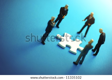 A business team around a puzzle piece.