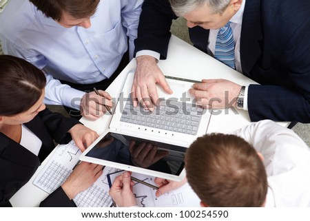 A business team of four sitting at table and planning