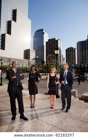 A business team portrait with large buildings in the background