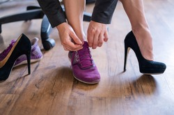 A business woman exchanges high heels for comfortable shoes in the workplace. A close-up of female hands takes off her black shoes and puts on colored sneakers in the office after a long working day.