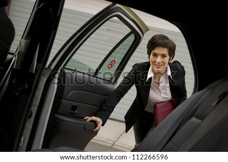 A business woman gets in the back seat of taxi cab downtown urban traveler