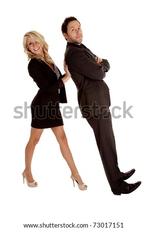 A business woman holding up her business man while he lays back on her hands.