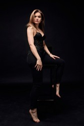 A business woman in a lace top and black pants sits on a high bar stool. Bare feet. Black background.