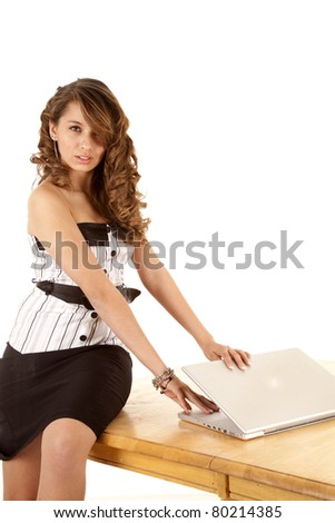 a business woman is trying to close her laptop so no one will see what she was doing.