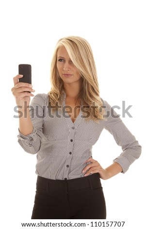A business woman looking at her phone not happy with what she is seeing.