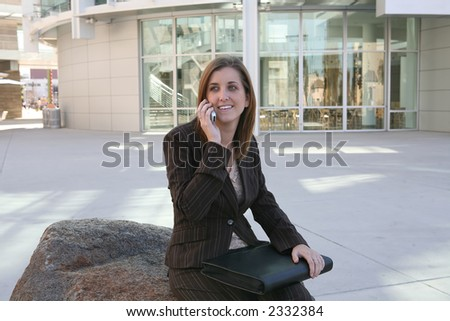 A business woman outside her workplace on the phone