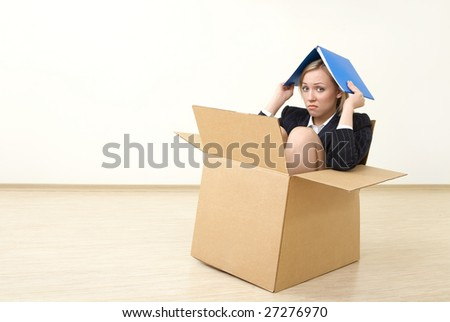 A business woman sits in a box, taking shelter a folder