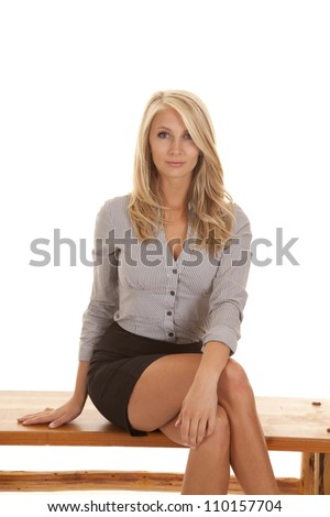 A business woman sitting on a bench with a small smile on her lips.