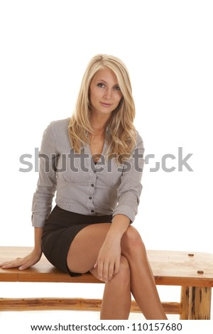 A business woman sitting on a wooden bench with a small smile playing at her lips.