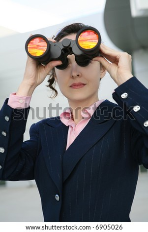 A business woman with binoculars outside her company