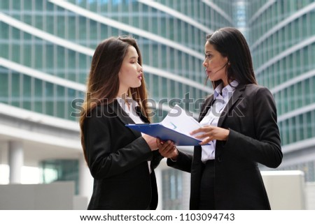 A business women of different ethnicities talk about finance looking at the patterns of economic markets and banks, and in the background a group of multi-ethnic business people. #1103094743