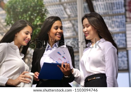 A business women of different ethnicities talk about finance looking at the patterns of economic markets and banks, and in the background a group of multi-ethnic business people. #1103094746