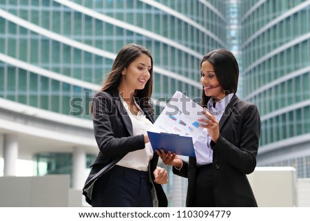 A business women of different ethnicities talk about finance looking at the patterns of economic markets and banks, and in the background a group of multi-ethnic business people. #1103094779